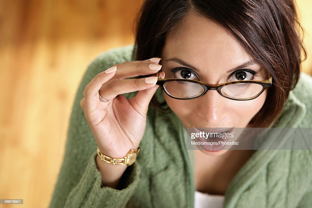 Close-up of a young woman holding her eyeglasses : Stock Photo