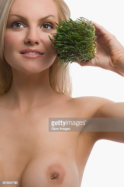 Close-up of a young woman holding wheatgrass and smiling
