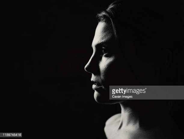 a closeup of a young woman in profile in dramatic light - moody sky stock pictures, royalty-free photos & images