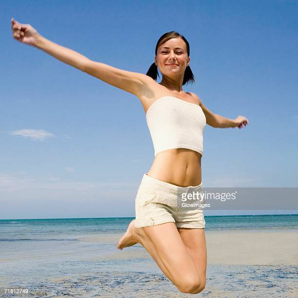 close-up of a young woman jumping on the beach - ombelico foto e immagini stock