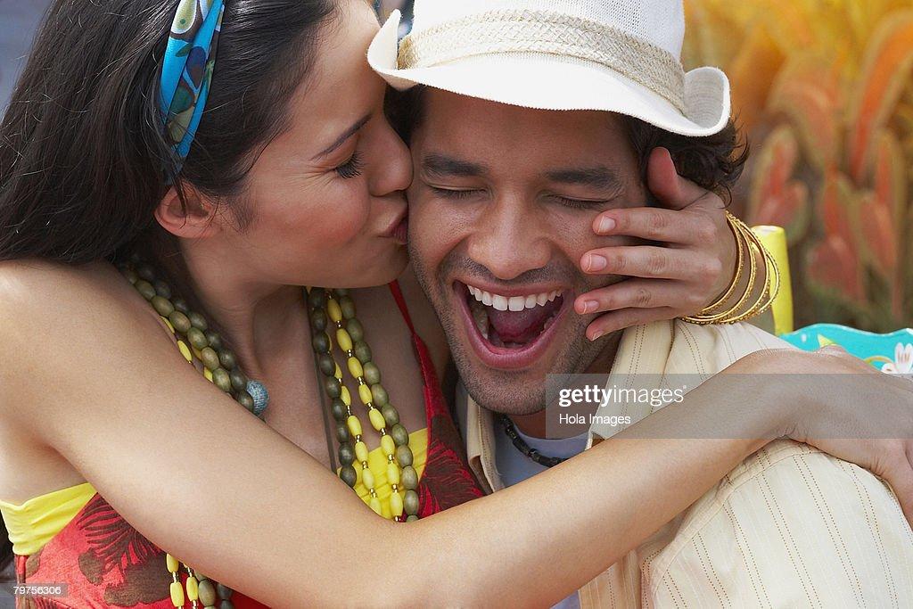 Close-up of a young woman kissing a young man : Foto de stock