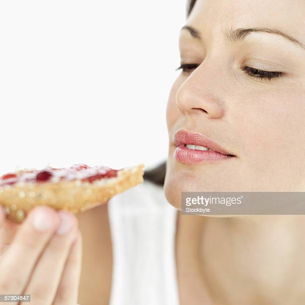 Close-up of a young woman looking at a slice of bread and jam in her hand