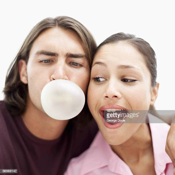 close-up of a young woman looking at a young man blowing a chewing gum bubble