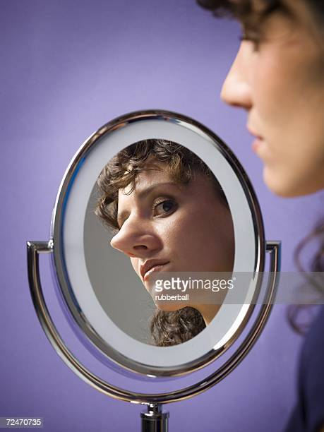 close-up of a young woman looking into a mirror - big nose stock photos and pictures