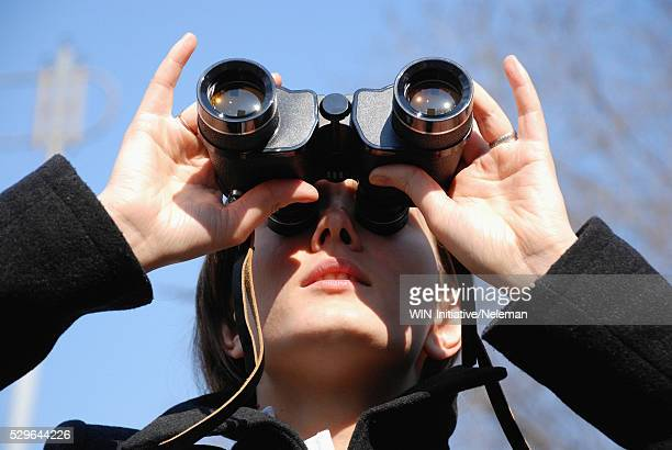 Close-up of a young woman looking through binoculars,