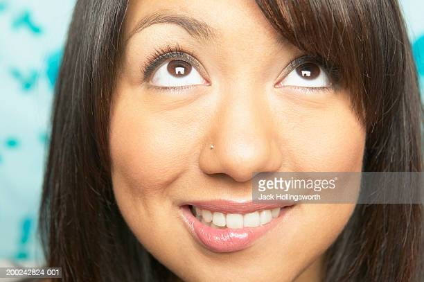 close-up of a young woman looking up - biting lip stock pictures, royalty-free photos & images