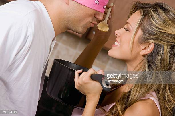 Close-up of a young woman making a blindfolded mid adult man to taste food