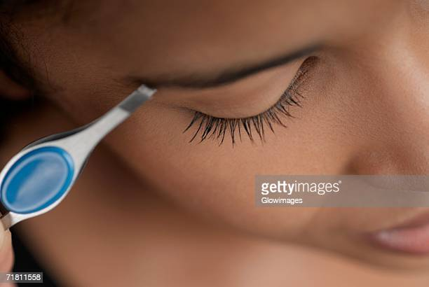 Close-up of a young woman plucking her eyebrows
