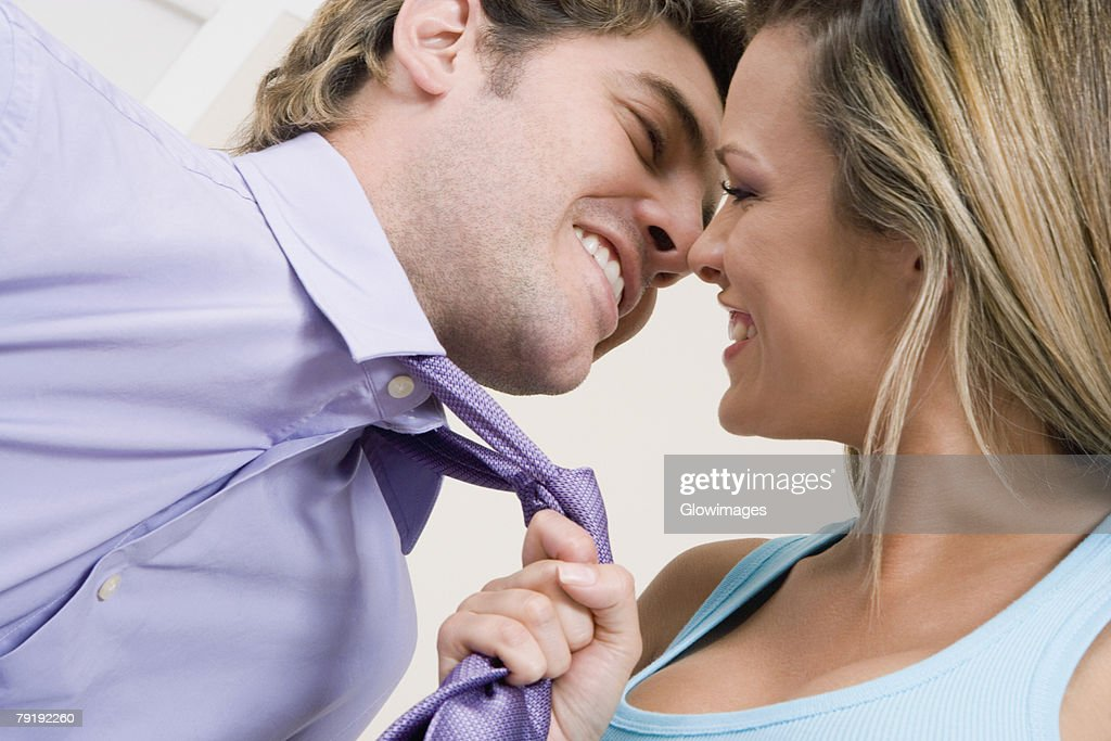 Close-up of a young woman pulling a mid adult man towards her with his tie : Foto de stock