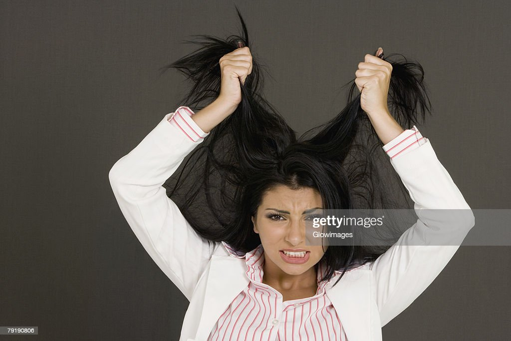 Close-up of a young woman pulling her hair : Stock Photo