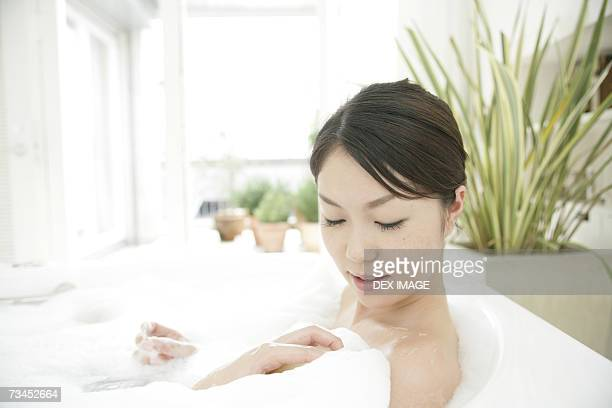 Close-up of a young woman relaxing in a bubble bath and smiling