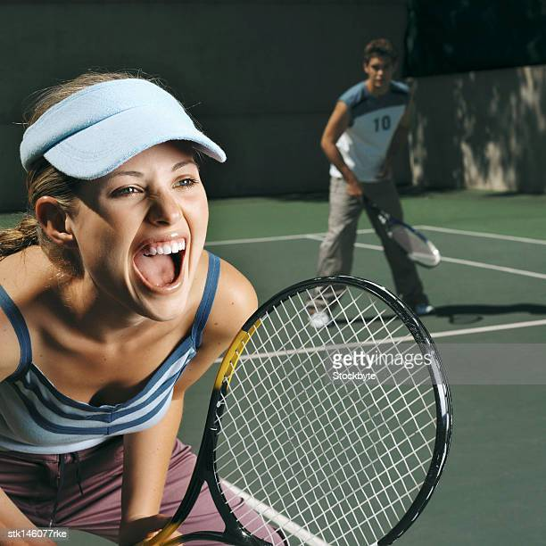 close-up of a young woman shouting while playing a mixed doubles game of tennis