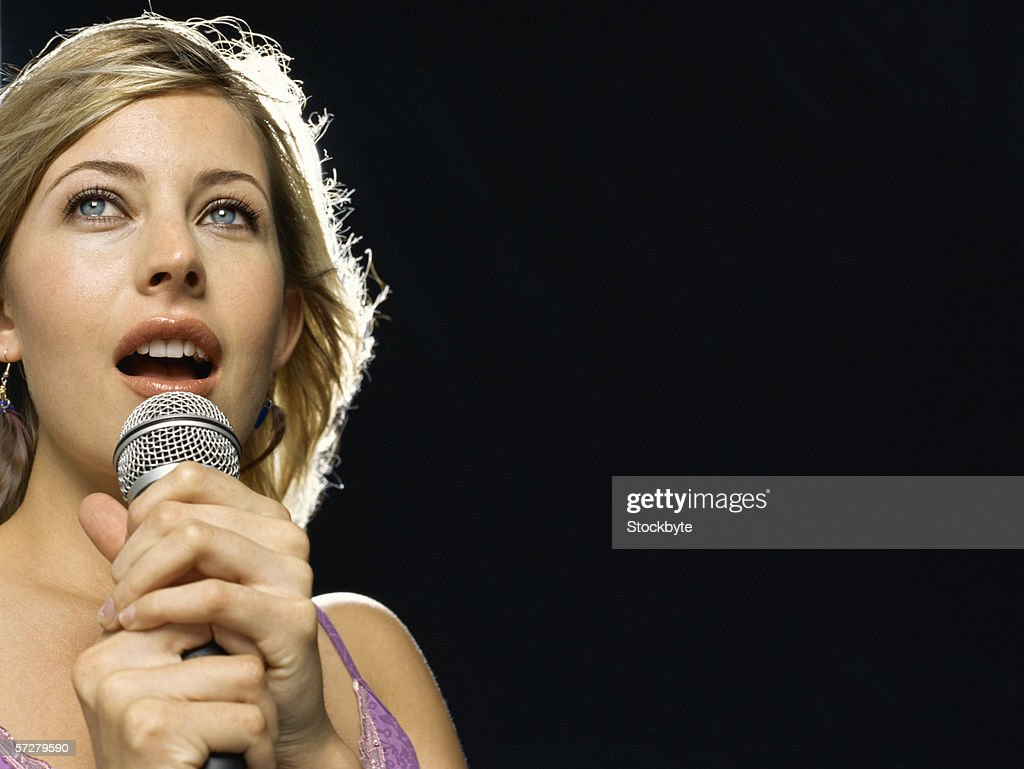 Close-up of a young woman singing : Stock Photo