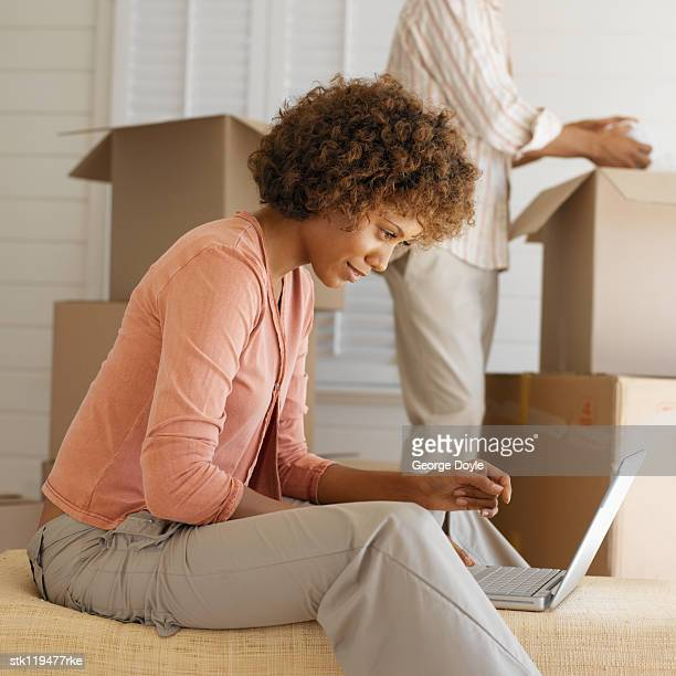 Close-up of a young woman sitting beside cardboard boxes working on a laptop