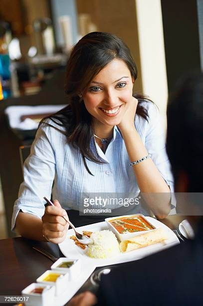 Close-up of a young woman sitting in a restaurant and eating