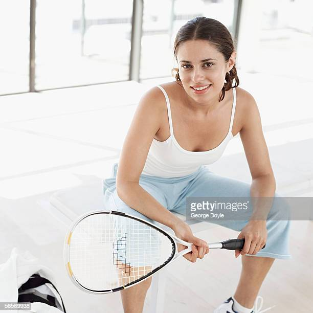 close-up of a young woman sitting on a bench holding a tennis racket