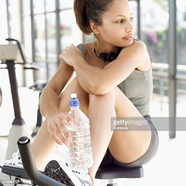 Close-up of a young woman sitting on an exercise bicycle holding a bottle of water