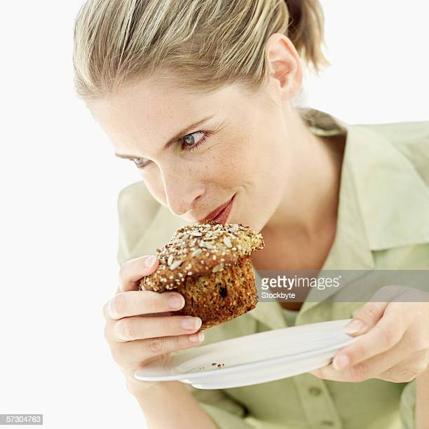 Close-up of a young woman smelling a muffin