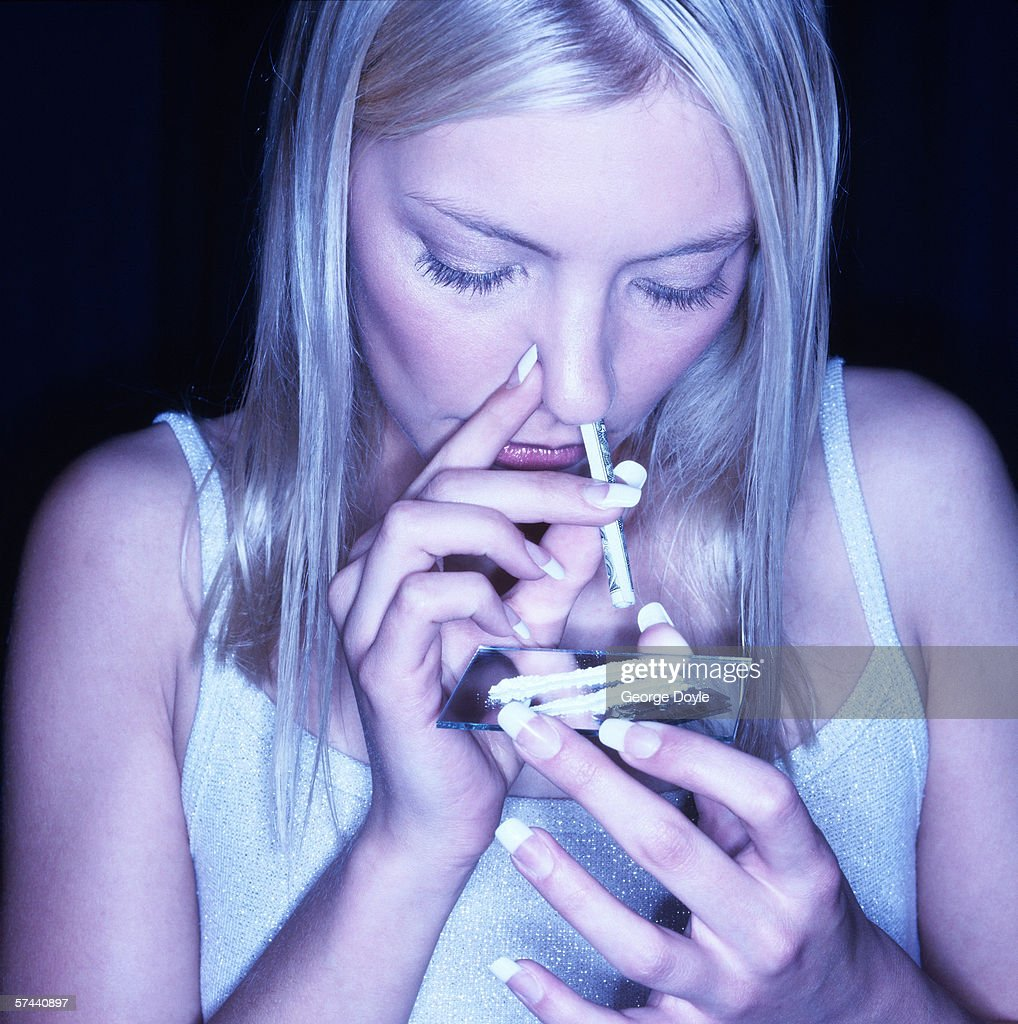 close-up of a young woman snorting drugs : Stock Photo