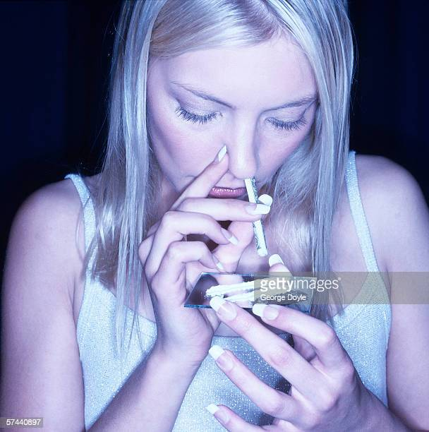 close-up of a young woman snorting drugs