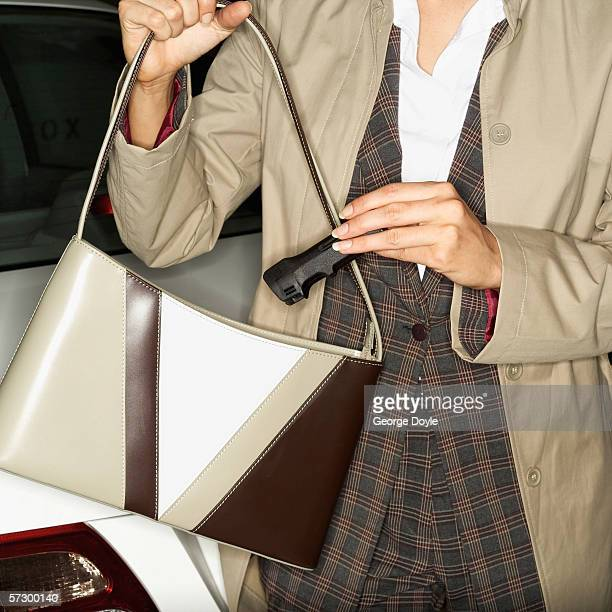close-up of a young woman taking pepper spray out of her handbag - pepper spray stock pictures, royalty-free photos & images