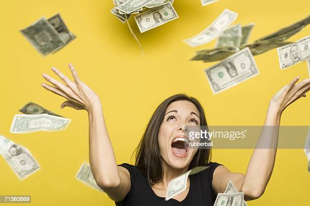 close-up of a young woman throwing american dollar bills in the air - exceed and excel stock pictures, royalty-free photos & images