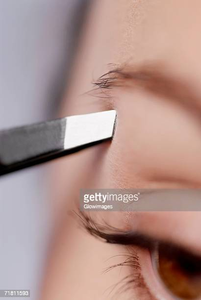 Close-up of a young woman tweezing her eyebrow