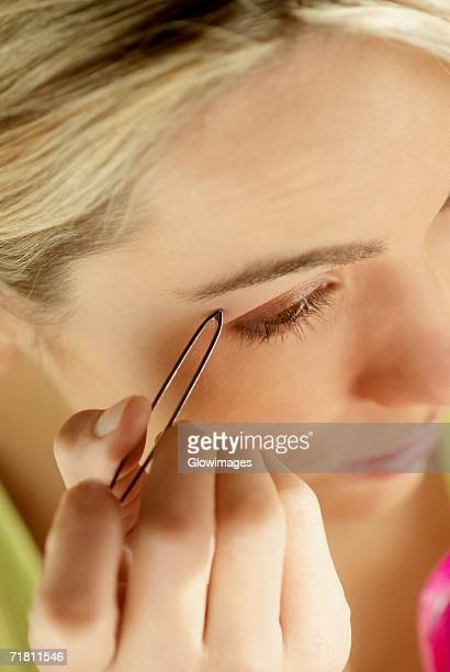 Close-up of a young woman tweezing her eyebrows