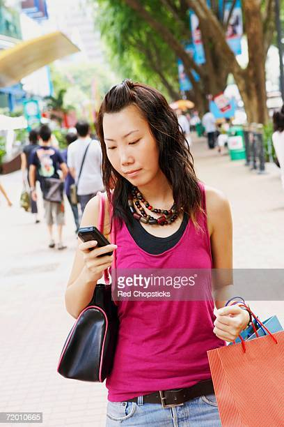 Close-up of a young woman using a mobile phone carrying shopping bags