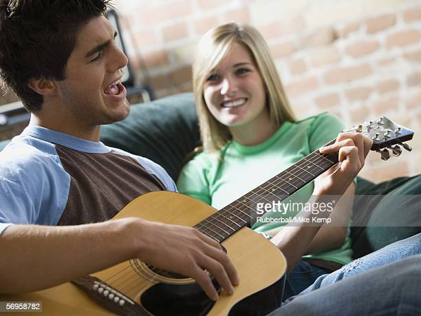 Close-up of a young woman watching a young man a play guitar
