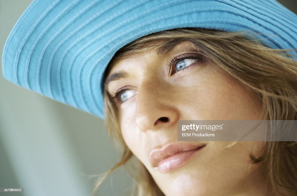 Close-Up of a Young Woman Wearing a Blue Sunhat, Looking Away Pensively : Stock Photo