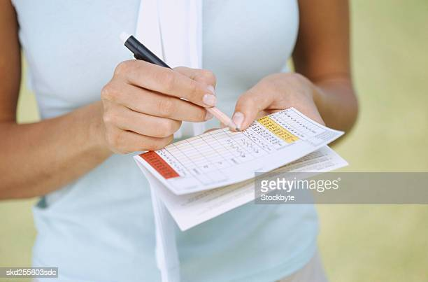 close-up of a young woman writing on a scorecard - scoring stock pictures, royalty-free photos & images