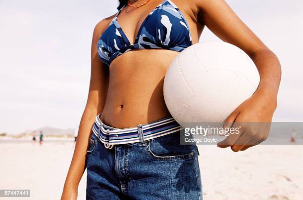 close-up of a young woman's bare midriff with her arm holding a ball to it