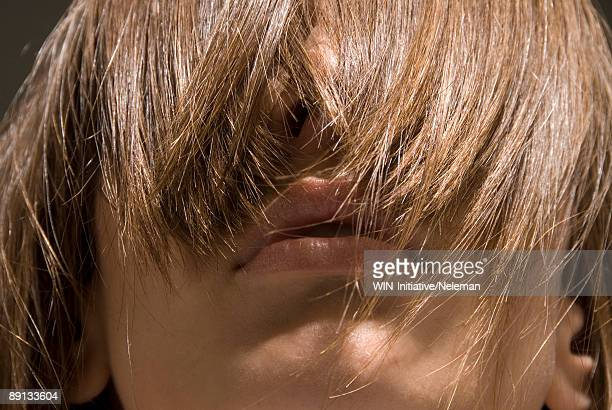 close-up of a young woman's eyes covered with her hair - junge frau rätsel stock-fotos und bilder