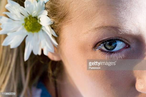 Close-up of a young woman's face, one eye and a flower in her hair visible