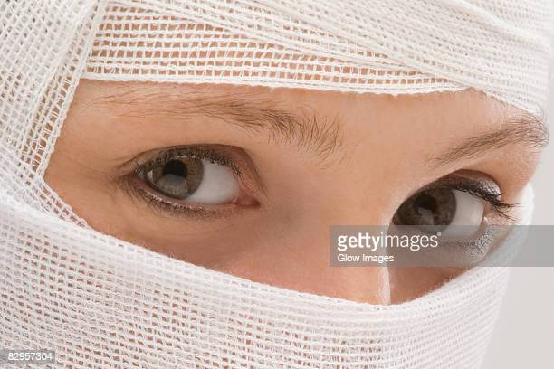 Close-up of a young woman's face wrapped with a bandage