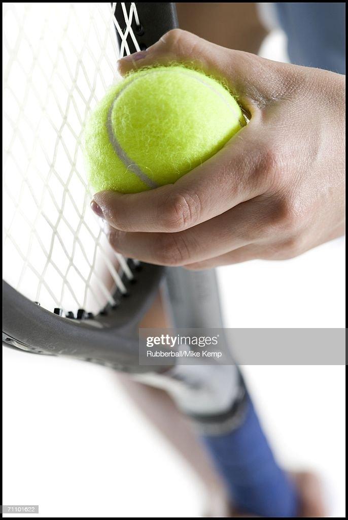 Close-up of a young woman's hand holding a tennis ball and a tennis racket : Stock Photo