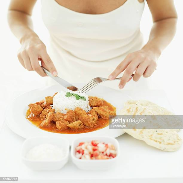 Close-up of a young woman's hands mixing white rice with curry on a plate