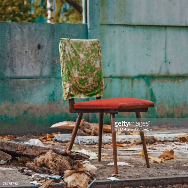 Close-Up Of Abandoned Chair On Footpath
