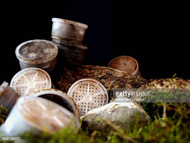 Close-Up Of Abandoned Coffee Capsules On Grass Against Black Background