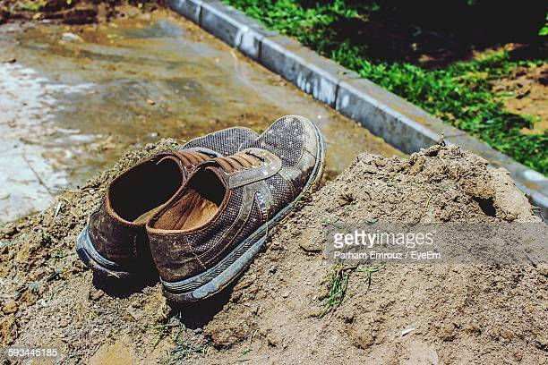 close-up of abandoned shoes on dirt heap - parham emrouz stock pictures, royalty-free photos & images