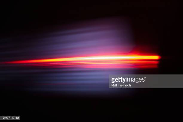close-up of abstract red light trail against black background - licht stock-fotos und bilder