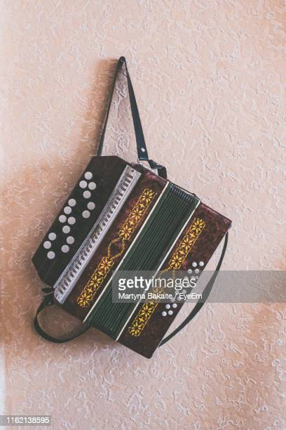 close-up of accordion hanging on wall - accordion stock pictures, royalty-free photos & images