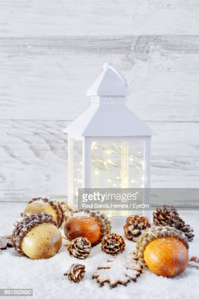 close-up of acorns by illuminated lantern on snow - christmas still life stock pictures, royalty-free photos & images