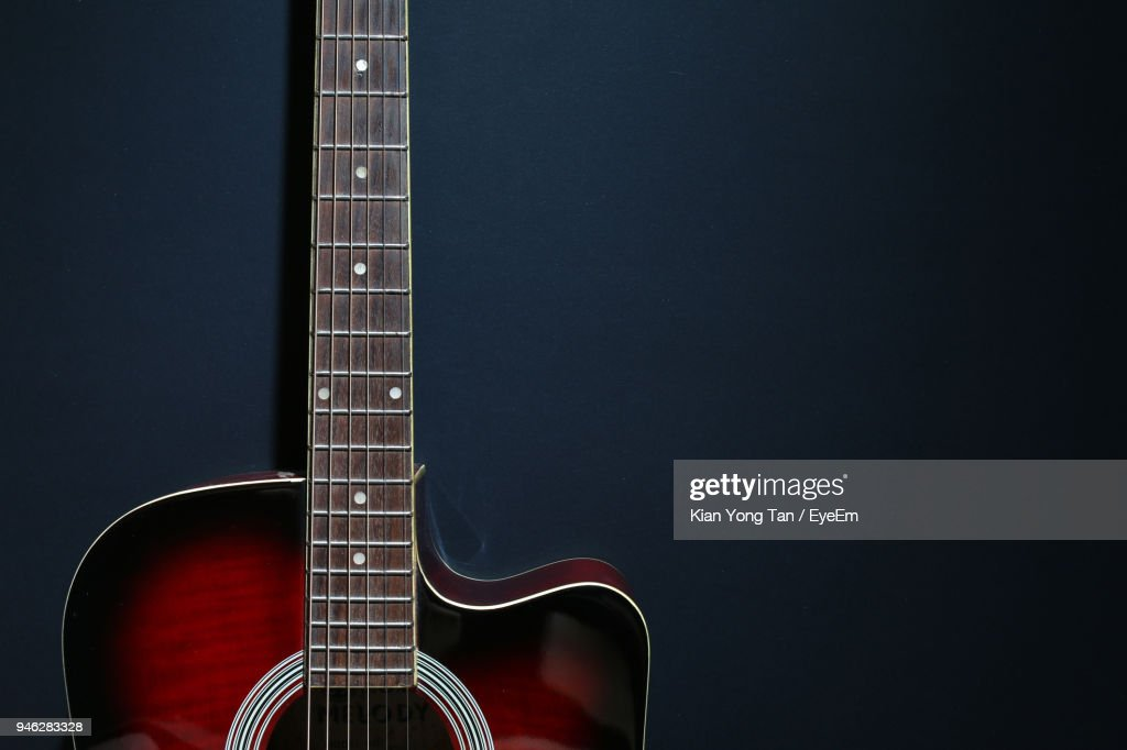Closeup Of Acoustic Guitar Against Black Background Stock Photo