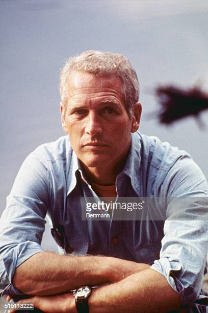 Closeup of actor Paul Newman sitting at table leaning on both arms crossed in front He made trip here for TV special