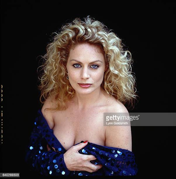 Closeup of actress Beverly D'Angelo exposing her cleavage and staring straight ahead She is wearing a blue offtheshoulder piece which she is holding...
