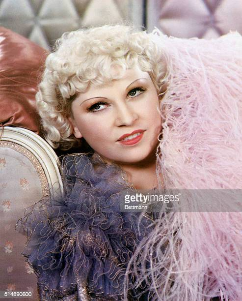 Close-up of actress Mae West. She is reclining in a pink boa. Undated photograph.