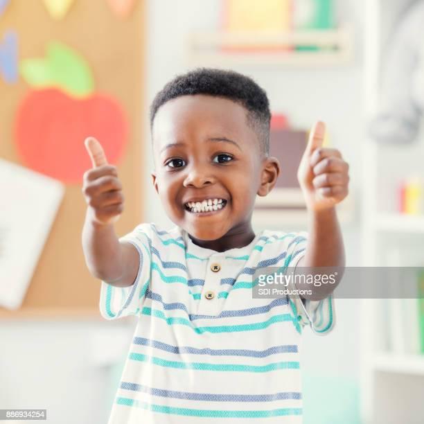 Closeup of adorable boy giving thumbs up at preschool