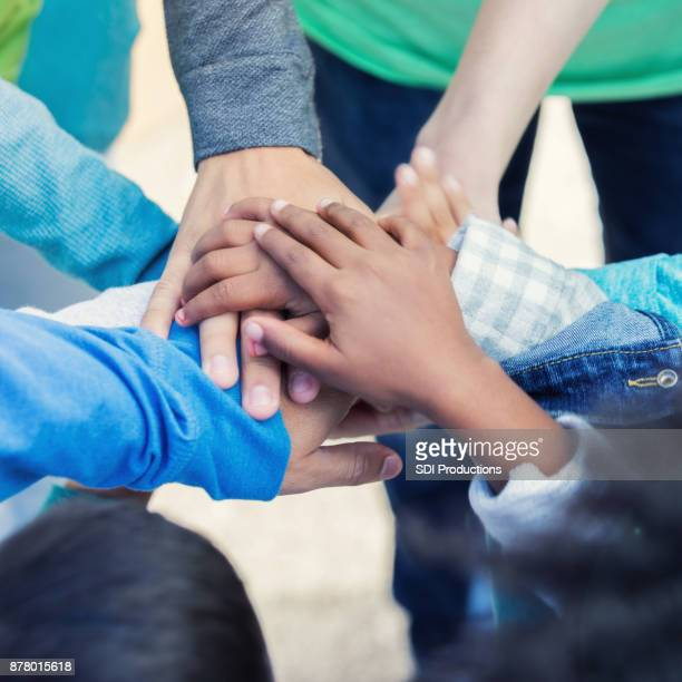closeup of adult and children stacking hands together outside - hands clasped stock pictures, royalty-free photos & images